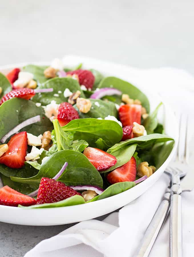 Front closeup view of strawberry spinach salad in a white bowl.