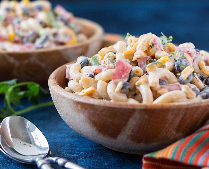 Front closeup of pasta salad in a wood bowl by a spoon.