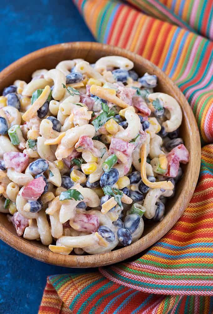 Overhead closeup of pasta salad in a wood bowl by a striped napkin.