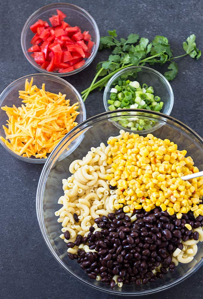 Overhead view of bowls of tomatoes, cheese, onions, corn, black beans and pasta.