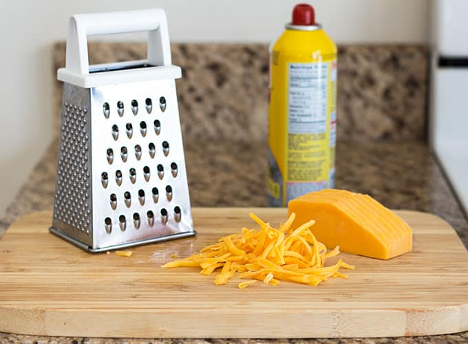 A grater beside cheese on a wood cutting board on a counter.