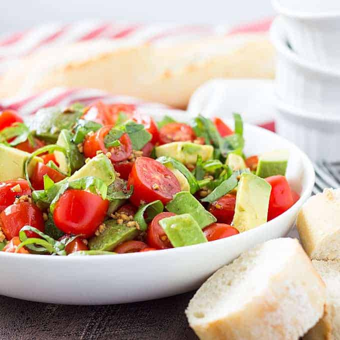 Front view of avocado and tomato salad in a white bowl beside slices of French bread.