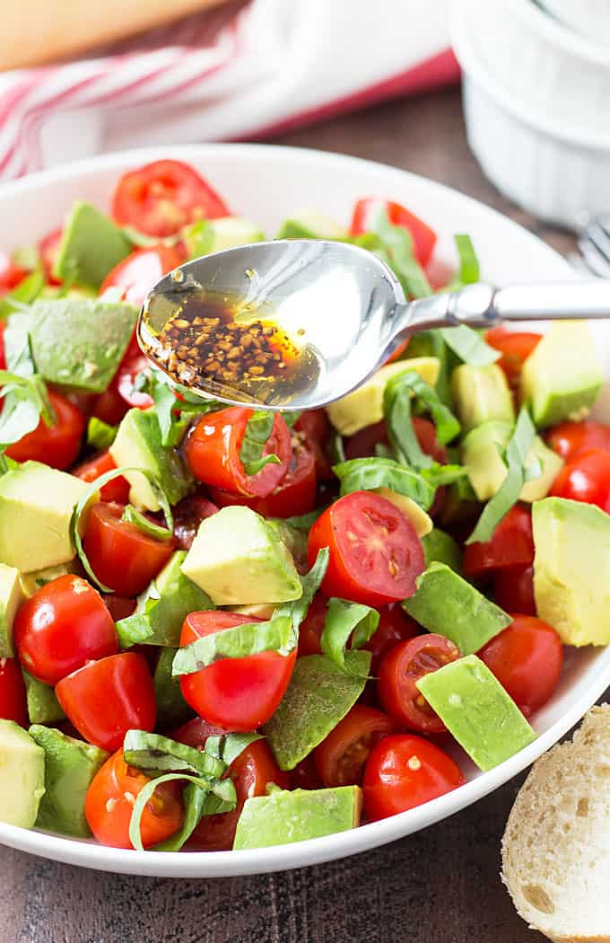 A spoon drizzling balsamic vinaigrette over a tomato and avocado salad in a white bowl.