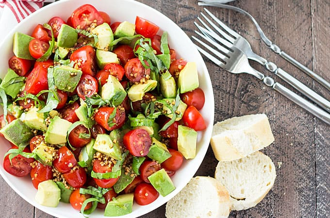 Overhead view of tomato salad in a white bowl beside three forks and sliced French bread.