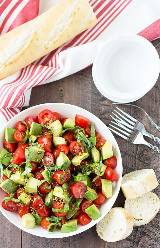 Overhead view of tomato and avocado salad in a white bowl.