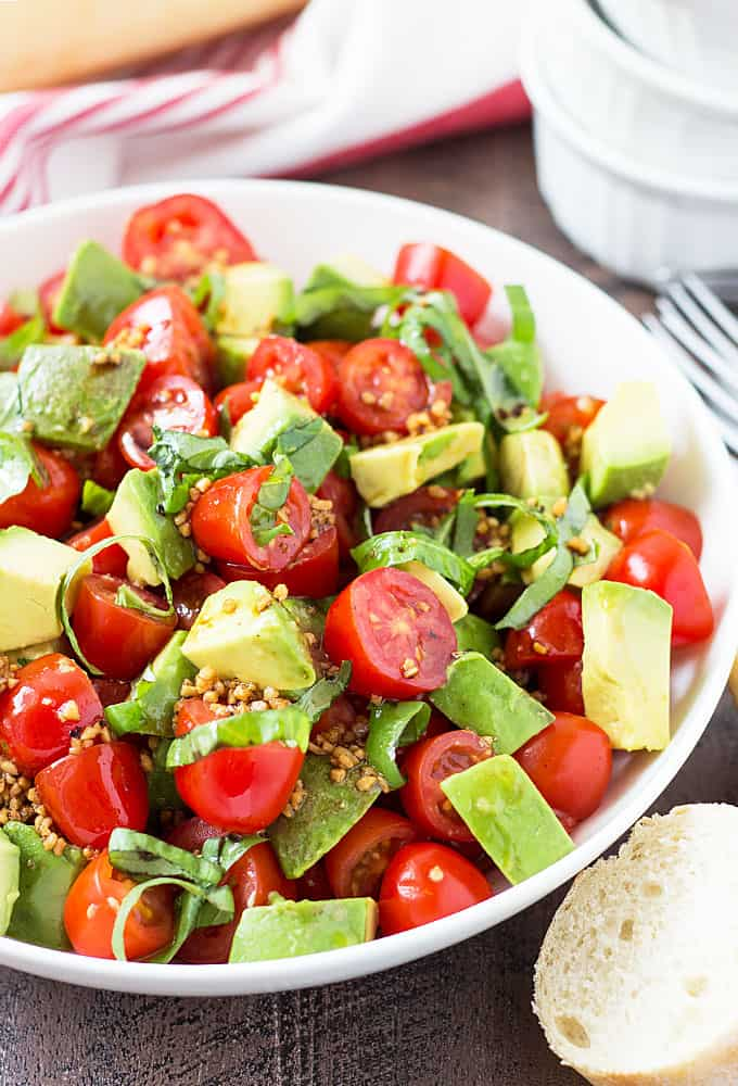 Closeup view of tomato salad with avocado and basil in a white bowl.
