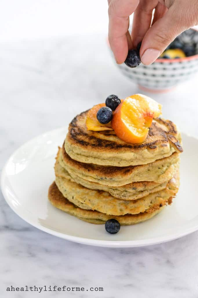 A stack of pancakes on a white plate topped with fresh peaches and blueberries.