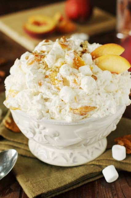 Peach Fluff Salad in a white decorative bowl over a folded napkin.
