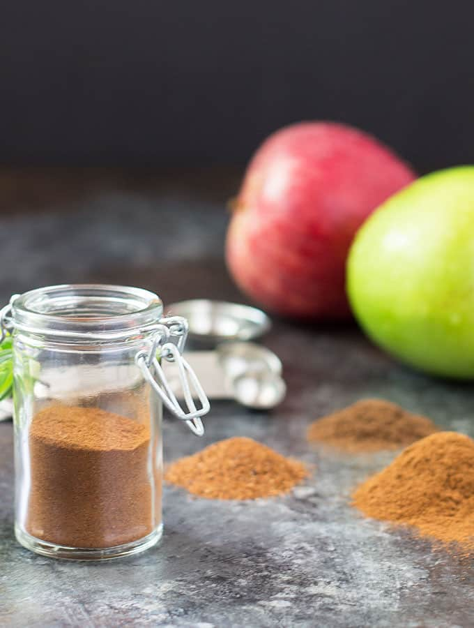 Front view of spice in a spice jar. Apples and measuring spoons are in background.