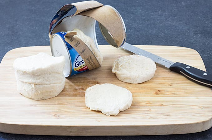 Canned biscuits on a wood cutting board with a knife.