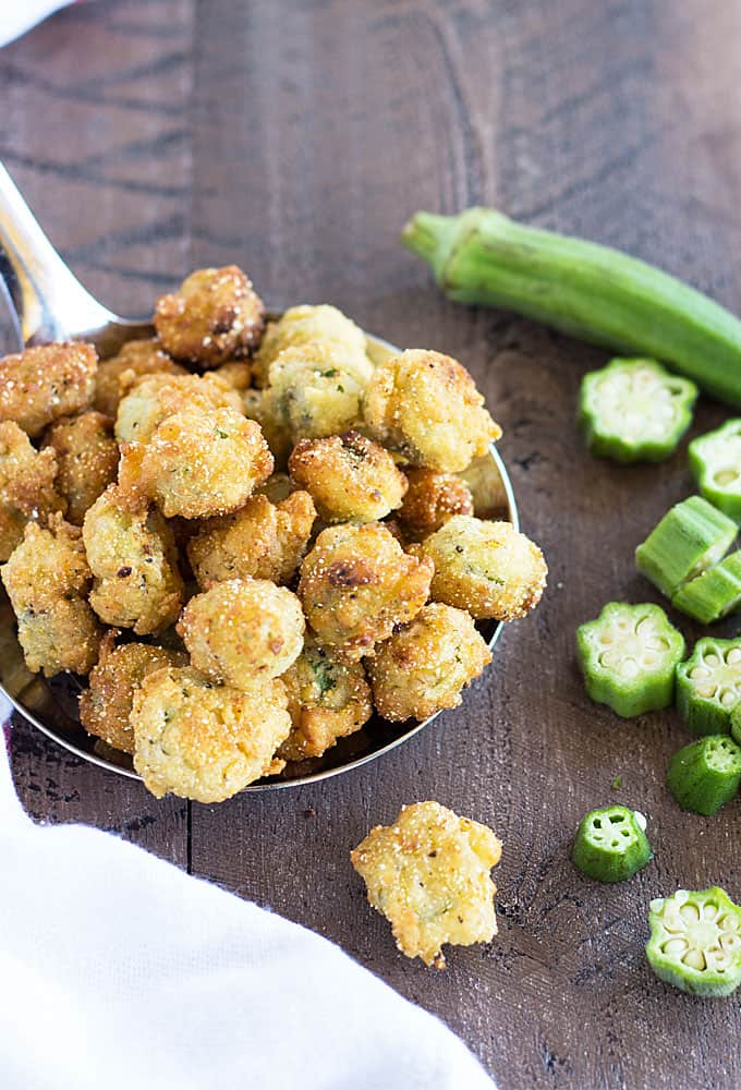 Closeup view of a large serving spoon filled with fried okra on a wood surface.