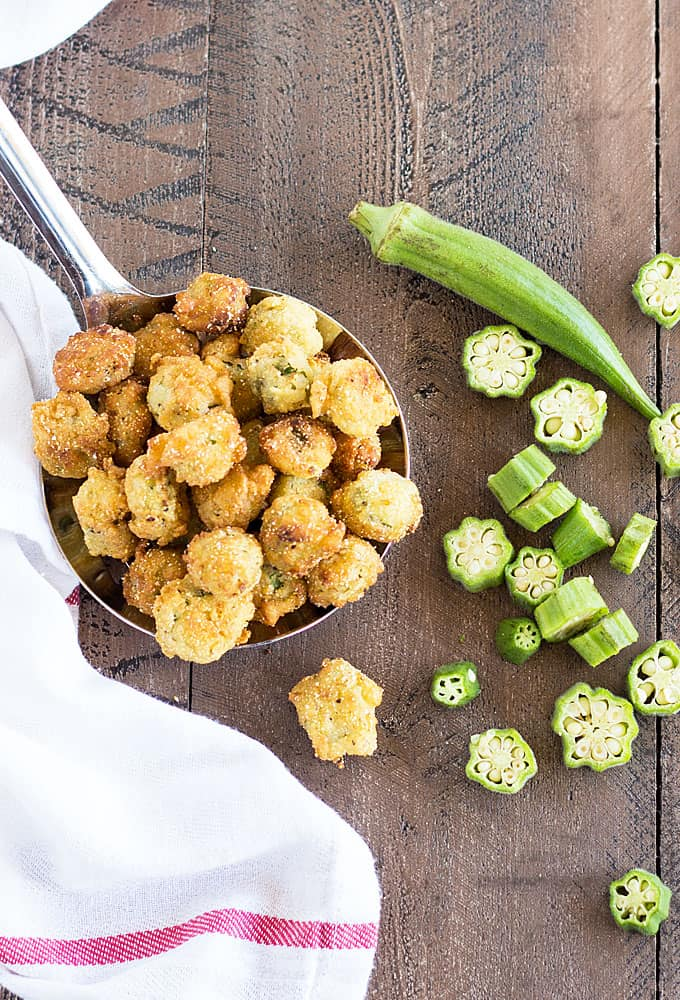 Overhead view of a large spoon filled with fried okra by a white napkin.