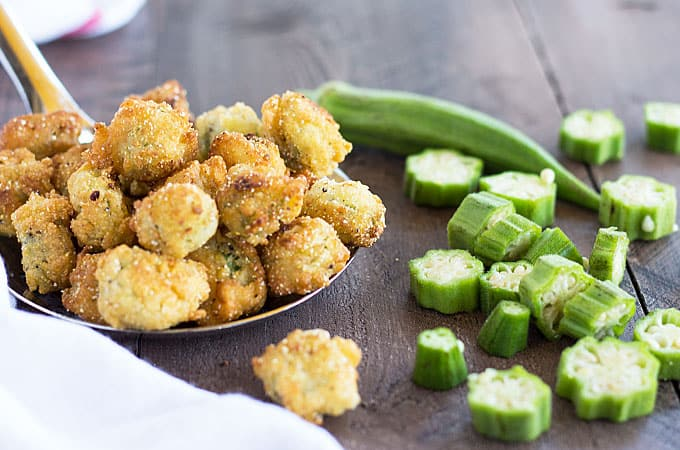 Closeup view of a spoonful of fried okra beside sliced fresh okra.