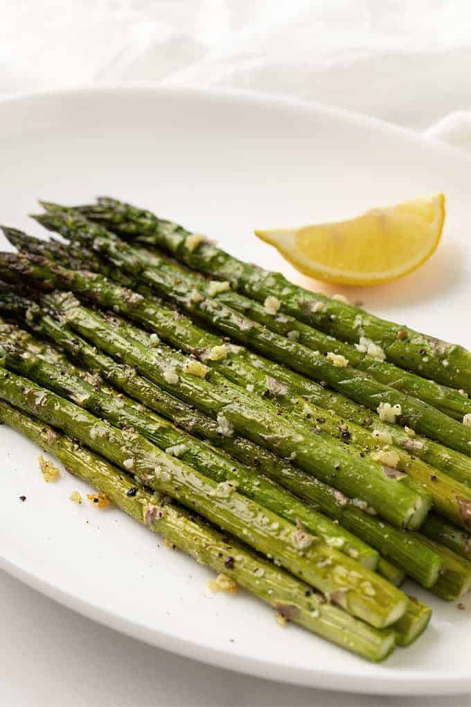 Baked asparagus with garlic on an oval white plate