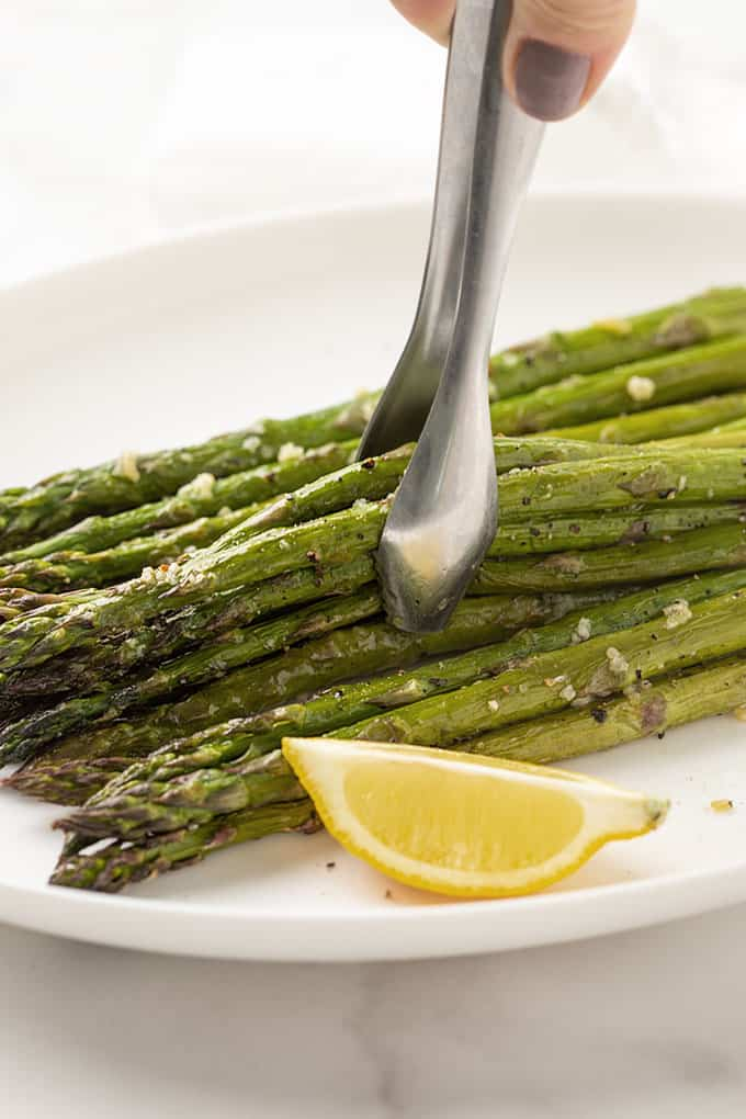 Garlic roasted asparagus on a white plate with a lemon wedge and set of tongs