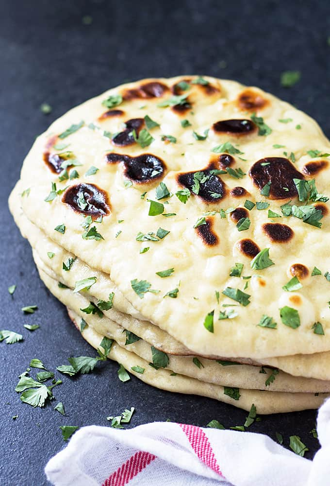 Angled overhead view of a stack of naan bread sprinkled with chopped fresh cilantro.