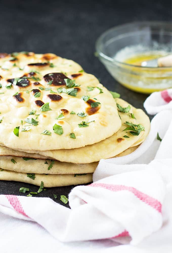 Front view of a stack of naan by a white napkin and a bowl of melted butter.