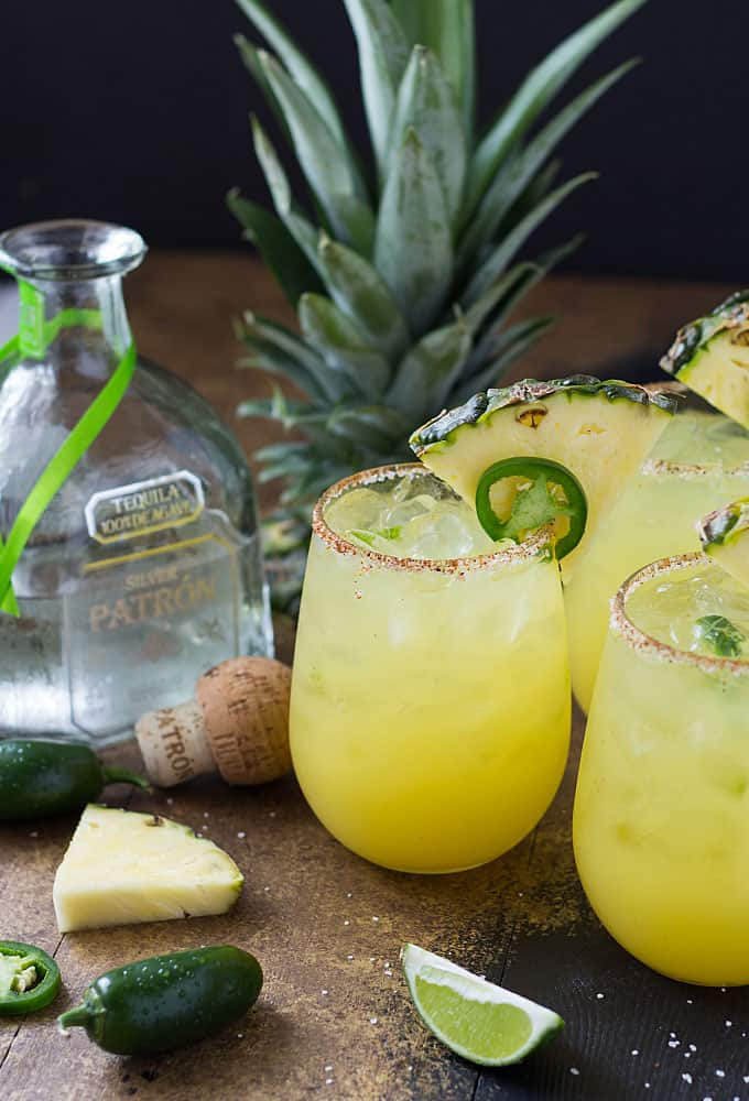 Three margaritas garnished with pineapple and jalapeno by a bottle of tequila.