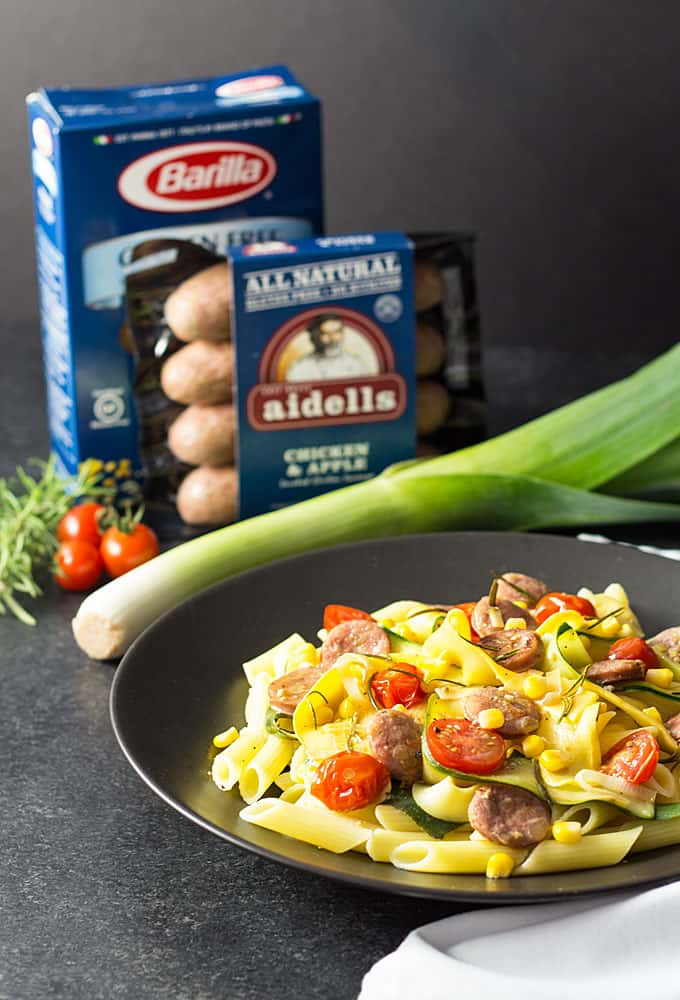 Pasta topped with sausage and vegetables on a black plate. A box of pasta and package of sausage is in the background.