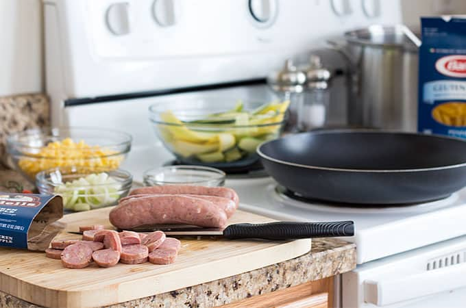 Sliced sausage on a cutting board with a knife on a granite kitchen counter.
