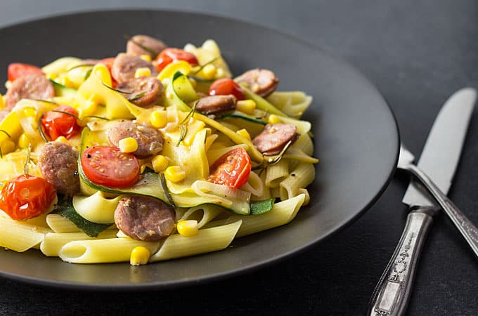 Front view of sausage, pasta and vegetables on a plate beside a fork and a knife.