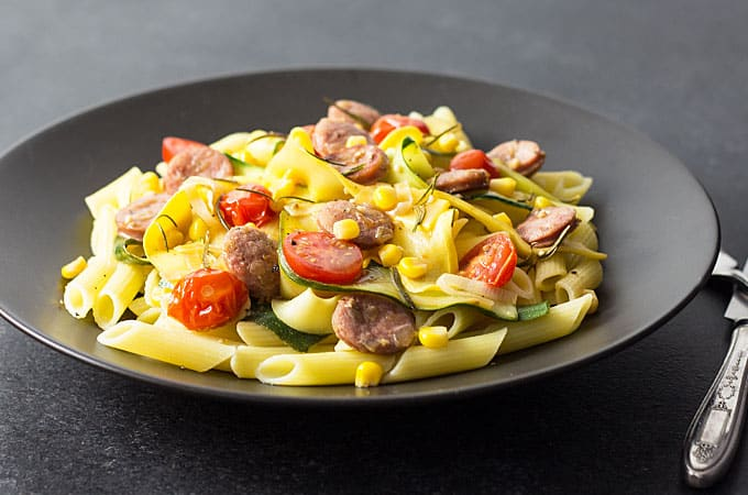 Front view of sliced sausage, pasta and vegetables on a black plate.