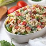BLT Pasta Salad in an oval white serving bowl beside a wooden serving spoon and white kitchen towel.