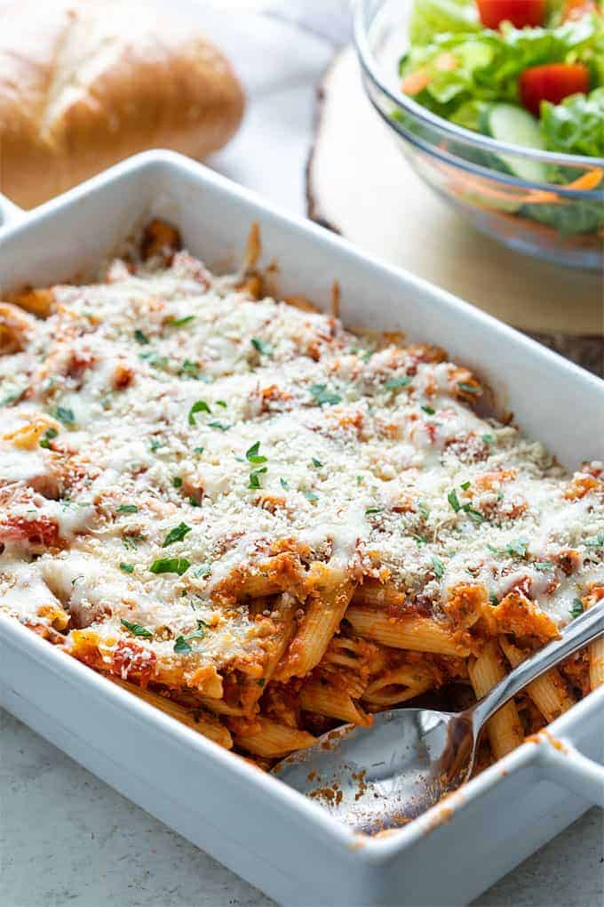 Chicken Parmesan Casserole in a white baking dish with a serving spoon