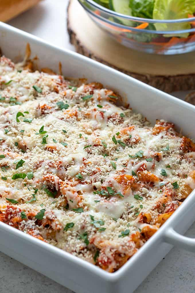 Chicken Parmesan Casserole in a baking dish with a salad and French bread in the background.