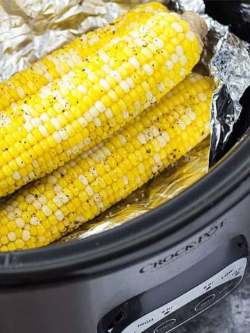 Three ears of corn on the cob in a slow cooker with aluminum foil.