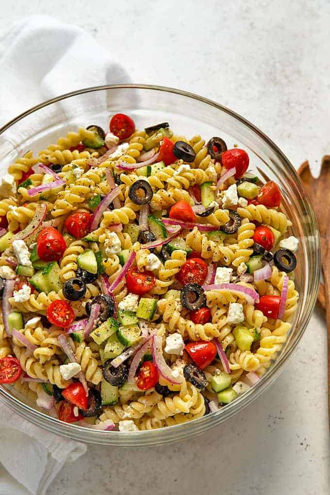 Overhead view of pasta salad in a large glass bowl by a wooden salad server.