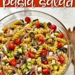 """A bowl of pasta salad with overlay text that reads """"Greek pasta salad""""."""