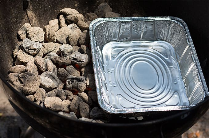 Coals and an aluminum tray in the bottom of a round outdoor grill.