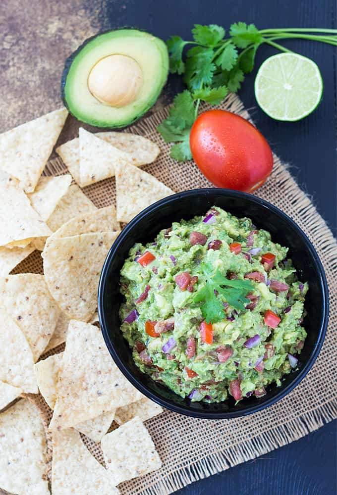 Bacon Chipotle Guacamole in a black bowl beside chips, an avocado, tomato, lime and cilantro