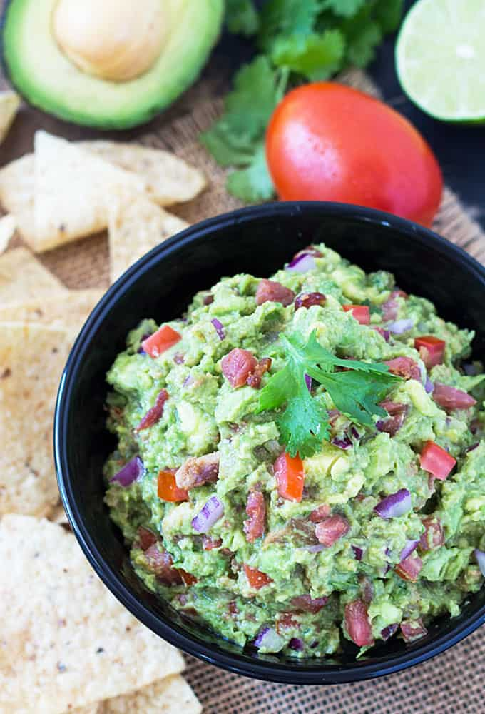 Bacon Chipotle Guacamole in a round black bowl beside tortilla chips