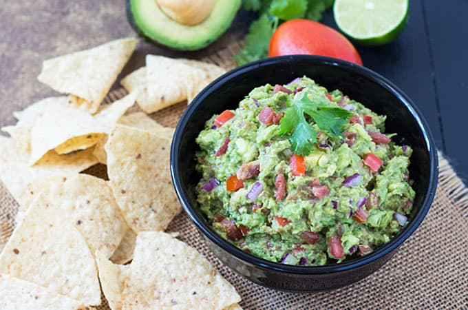 Bacon Chipotle Guacamole in a black bowl beside tortilla chips