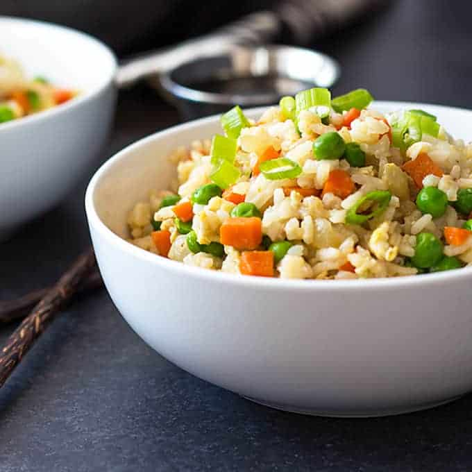 Front closeup view of fried rice with vegetables in a white bowl beside chopsticks.