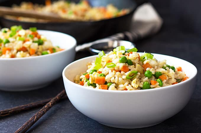 Front view of two bowls of rice with peas, carrots and cooked egg beside chopsticks.