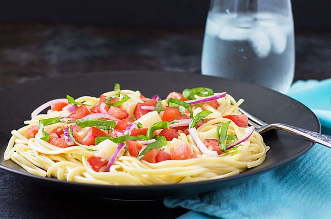 Front view of Marinated Tomato and Mozzarella Pasta on a black plate with a glass of water in the background