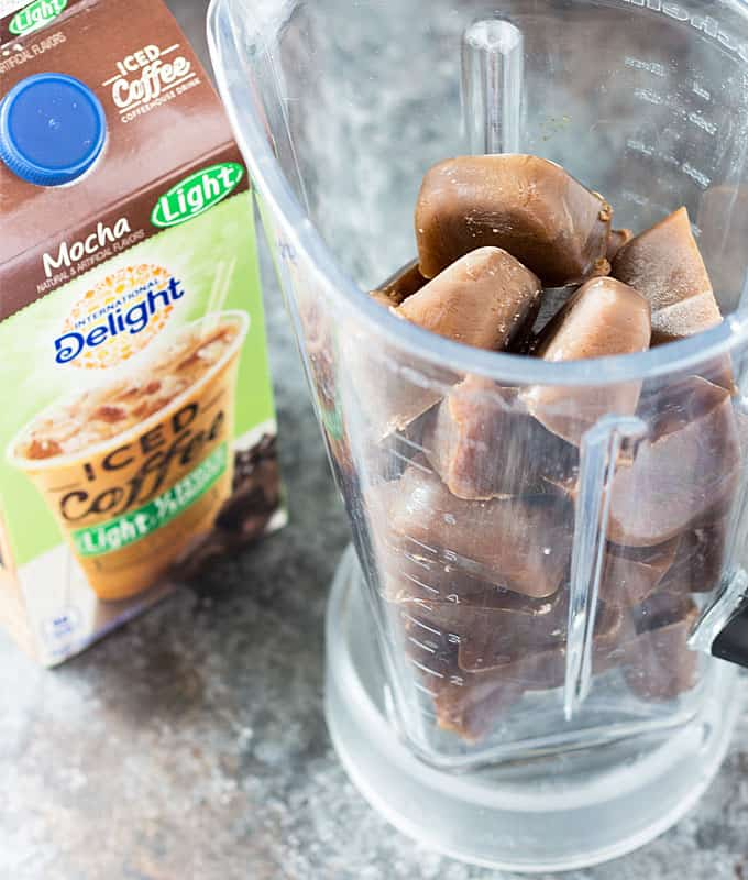Frozen iced coffee in a blender pitcher beside a carton of iced coffee.