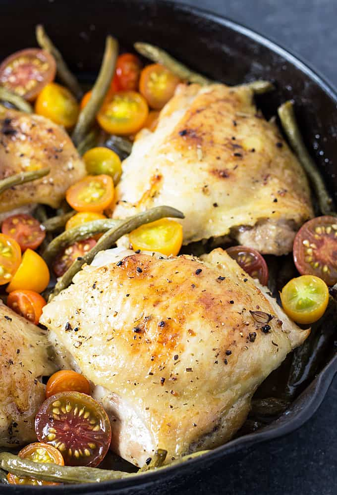 Roasted chicken, green beans and tomatoes in a cast iron skillet