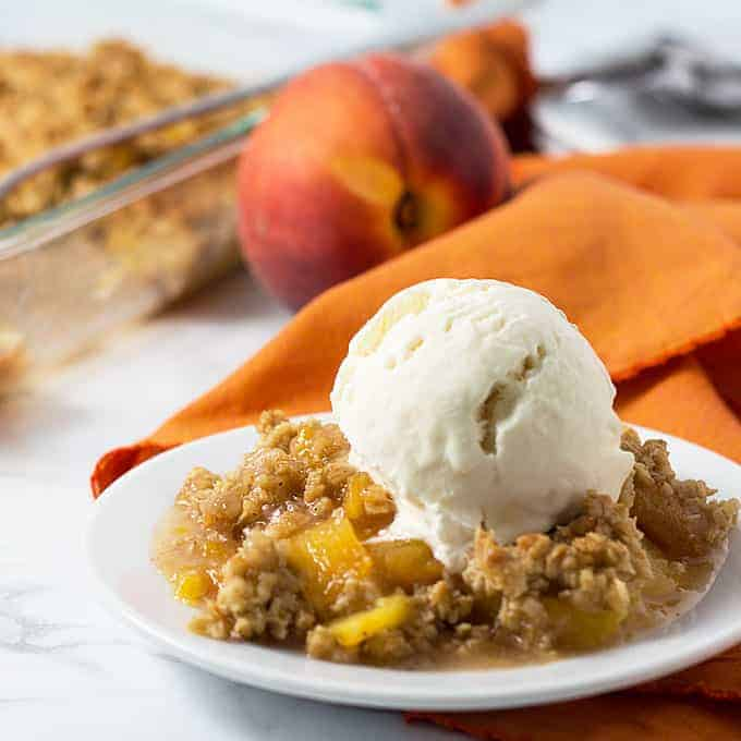 Front closeup view of peach crisp topped with vanilla ice cream on a white plate.