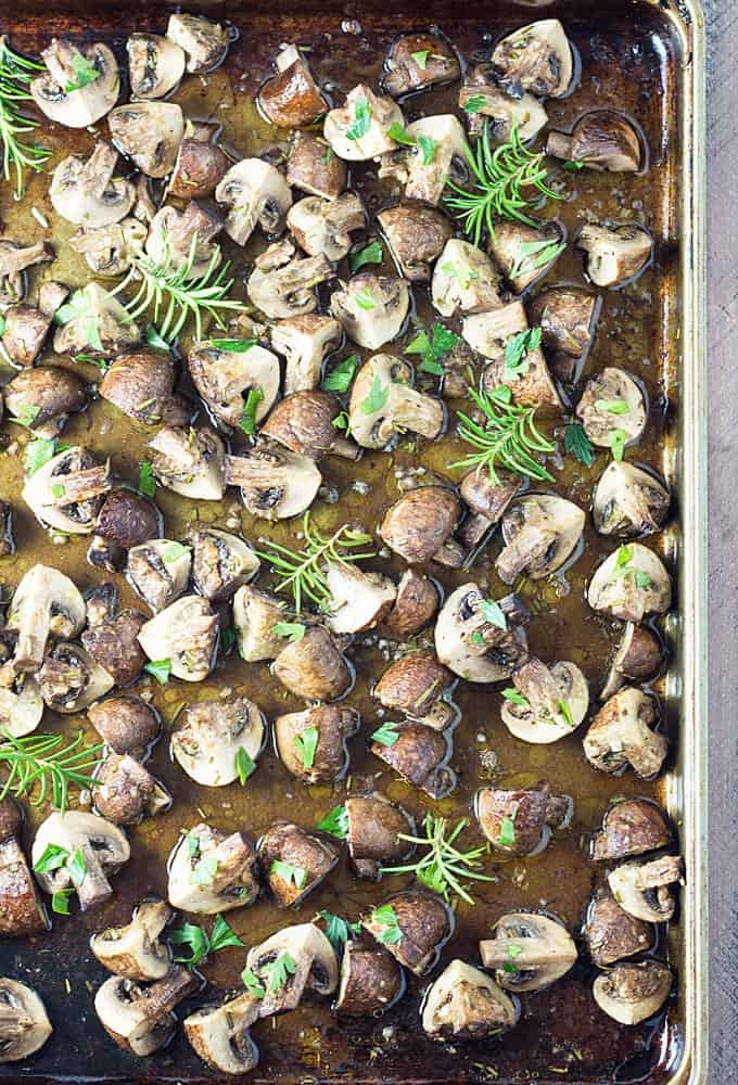 Overhead view of roasted mushrooms with garlic and rosemary on a baking sheet.
