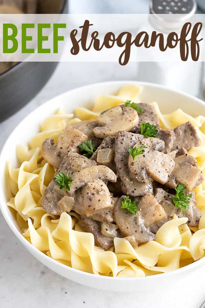 Beef stroganoff with mushrooms over egg noodles in a white bowl. Overlay text at top of image.
