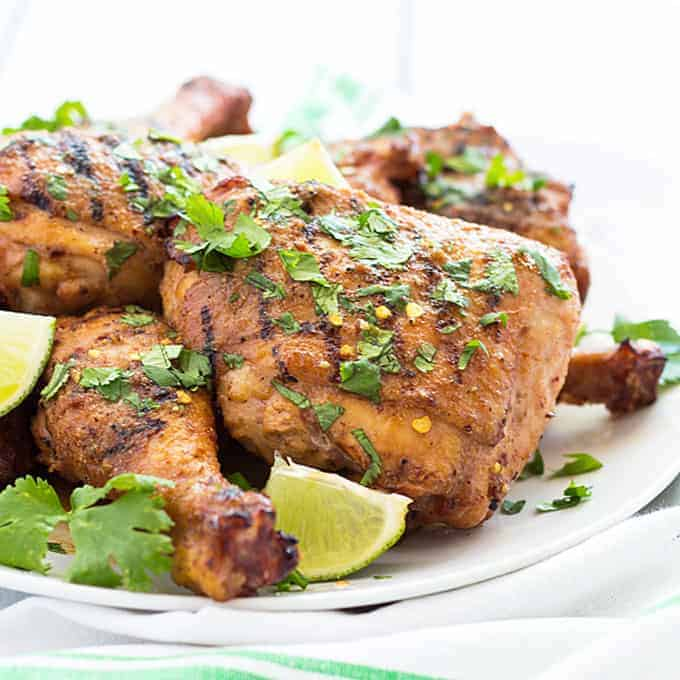 Front closeup view of grilled chicken topped with fresh cilantro and lime wedges on a white plate.