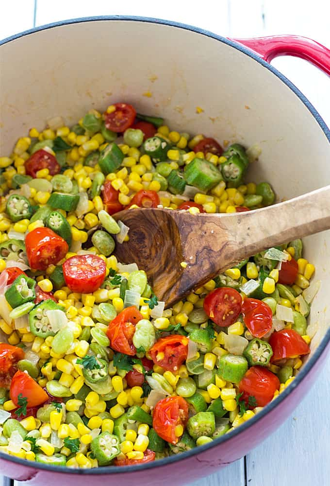 Overhead view of vegetable succotash in a red dutch oven with a wooden spoon.