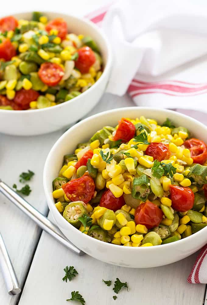 Two white bowls of vegetable succotash on a white surface by a striped kitchen towel.