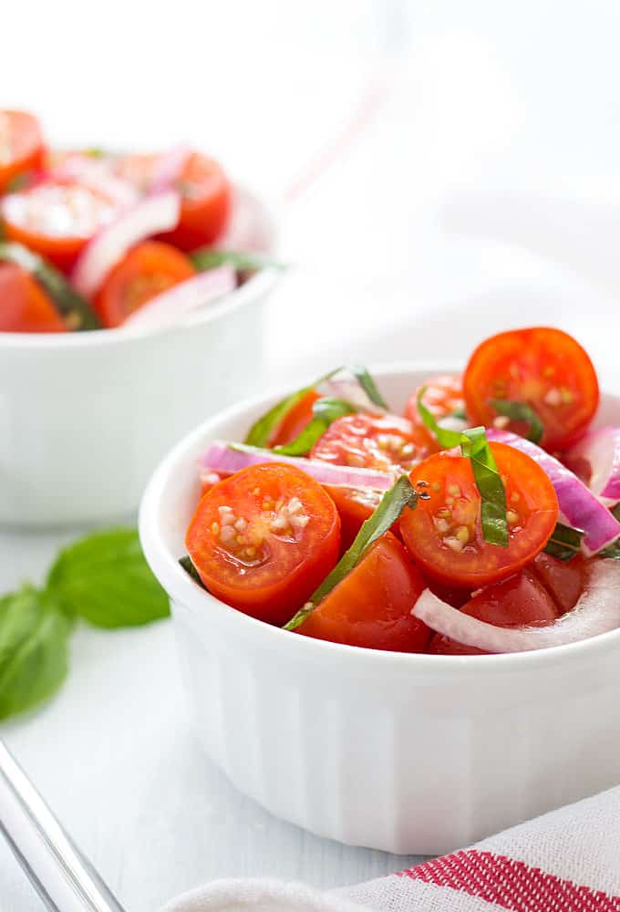 Front view of tomato basil salad with onion in a white ramekin.