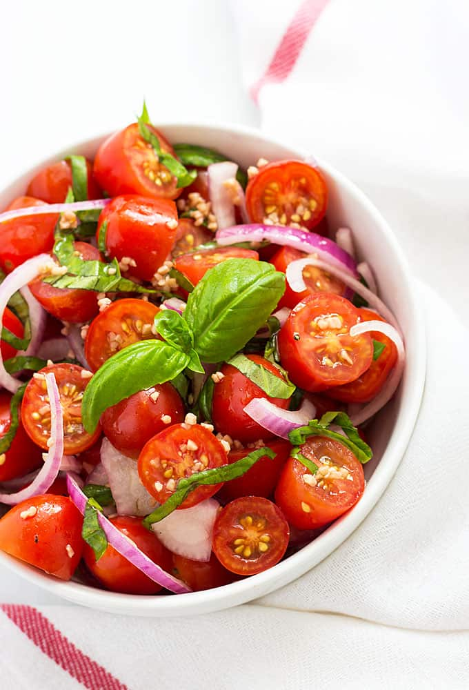 Overhead view of sliced cherry tomatoes with red onion and basil in a white ramekin.