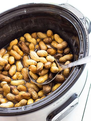 Overhead view of a ladle ladling boiled peanuts from a slow cooker.